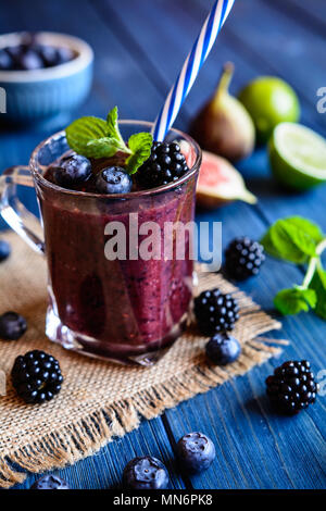 Healthy blackberry smoothie with figs, blueberry and lime in a glass jar - Stock Photo