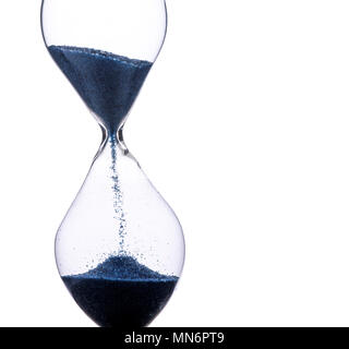 Hourglass dropping sand, running time, isolated on a white background, macro closeup with blue sand and lots of detail - Stock Photo