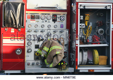 A firefighter's jacket and helmet rests on the side of a fire engine during a blaze. - Stock Photo