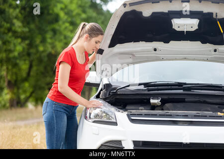 Portrait of young woman looking under the hood of her broken field on countryside road - Stock Photo