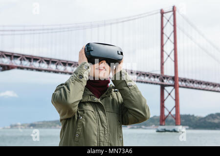 Young beautiful girl wearing virtual reality glasses. 25th of April bridge in Lisbon in the background. The concept of modern technologies and their use in everyday life - Stock Photo