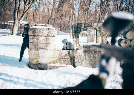 Paintball player hands with marker gun shooting at the enemy, winter forest battle. Extreme sport game - Stock Photo