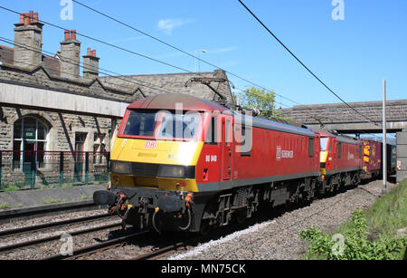 Class 90 electric trains in red DB Schenker livery hauling a container train along the West Coast Main Line passing through Carnforth. - Stock Photo