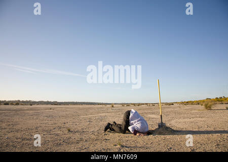A professional with his head buried in the sand. - Stock Photo