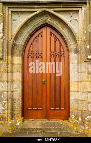 pair of oak wood church doors recently re stained and refurbished with stonework framing the entrance to a village church. - Stock Photo