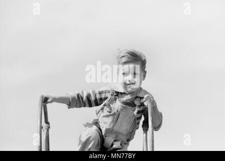 Portrait of Young Boy at Top of Playground Slide, Child of Migratory Worker, Weslaco, Texas, USA, Arthur Rothstein for Farm Security Administration, January 1942 - Stock Photo