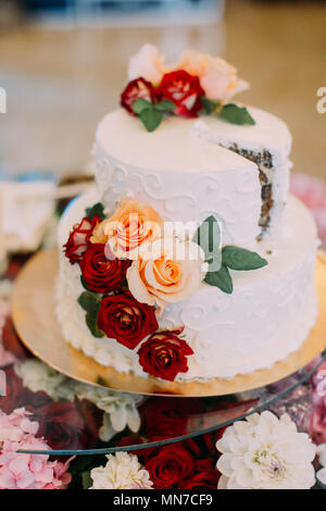 Vertical view of the white wedding cake decorated with red and orange roses. - Stock Photo