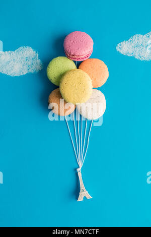 Eiffel tower model tied to macarons in form of balloons with strings flying up to the sugar clouds minimal creative concept. - Stock Photo