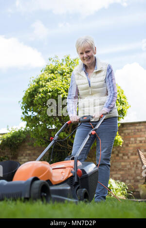 Senior Woman Using Electric Lawn Mower To Cut Grass At Home - Stock Photo