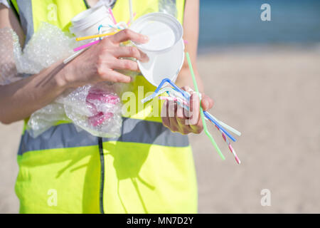Close Up Of Person Collecting Plastic Waste From Polluted Beach - Stock Photo