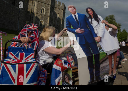 Royalists occupy benches outside Windsor Castle with a life-size standee of Prince Harry and Meghan Markle as the royal town gets ready for the royal wedding between Harry and his American fiance, on 14th May 2018, in London, England. - Stock Photo