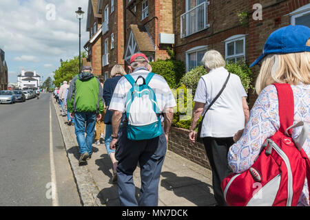 Group of elderly people with backpacks walking along a narrow pavement in the UK. - Stock Photo