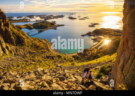 Hiker going to the top of mount Festvagtinden on Lofoten islands - Stock Photo