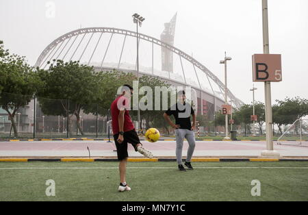 Doha, Qatar. 13th May, 2018. DOHA, QATAR - MAY 13, 2018: Teenagers play the ball by Khalifa International Stadium, a venue for 2022 FIFA World Cup football matches. Qatar is to host the FIFA World Cup in late 2022. Mikhail Aleksandrov/TASS Credit: ITAR-TASS News Agency/Alamy Live News - Stock Photo