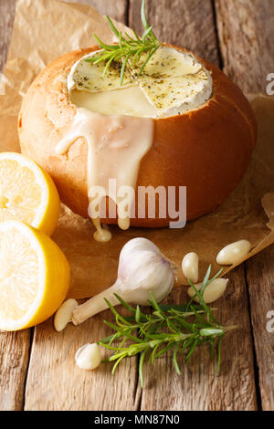 Fondue in a loaf of bread from melted camembert cheese close-up on a table. vertical - Stock Photo
