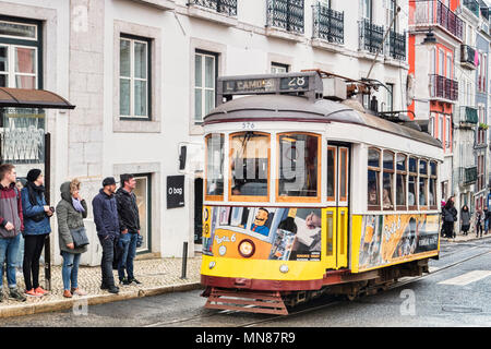 6 March 2018: Lisbon, Portugal - The famous 28 tram on its route in the central city. - Stock Photo