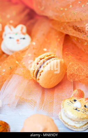 Orange macaroons with chocolate filling on orange tulle background - Stock Photo