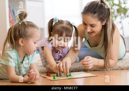 Mother and daughters sitting in a playroom, playing a ludo game and enjoying their time together - Stock Photo