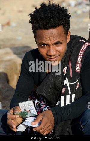 DJIBOUTI , Obock, from here ethiopian migrants try to cross bab el mandeb by boat to Yemen to go on to Saudi Arabia or Europe, ethiopian refugees from Tigray waiting outside the town for the smugglers, orthodox christians with cross scar on the forehead / DSCHIBUTI, Obock, Meerenge Bab el Mandeb, mit Hilfe von Schleppern aethiopische Migranten versuchen hier nach Jemen ueberzusetzen, um weiter nach Saudi Arabien oder Europa zu gelangen, aethiopische Fluechtlinge aus Tigray warten ausserhalb der Stadt auf die Schmuggler, orthodoxe Christen mit auf der Stirn in die Haut eingeritztem Kreuz - Stock Photo