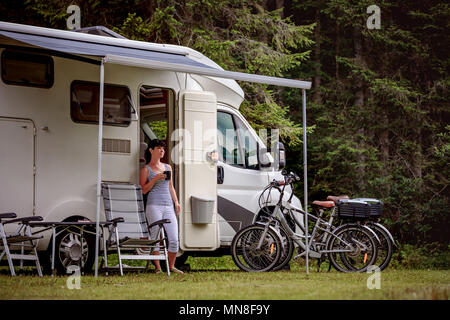 Woman is standing with a mug of coffee near the camper. Caravan car Vacation. Family vacation travel, holiday trip in motorhome RV - Stock Photo