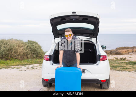 Man standing in back of car smiling and getting ready to go. Young laughing mle standing near open trunk of a car. Summer road trip - Stock Photo