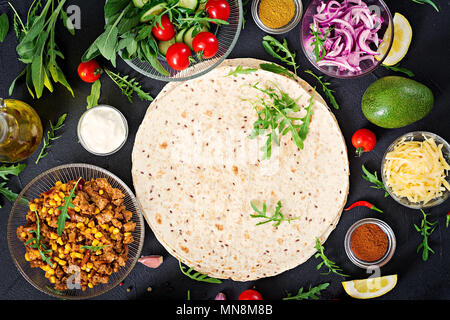 Ingredients for burritos wraps with beef and vegetables on black background. Mexican food. Top view. Flat lay - Stock Photo