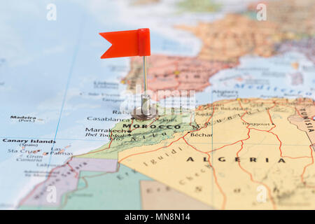 Small red flag marking the African country of Morocco on a world map. - Stock Photo