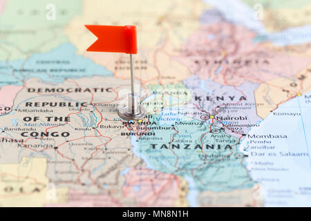 Small red flag marking the African country of Rwanda on a world map. - Stock Photo