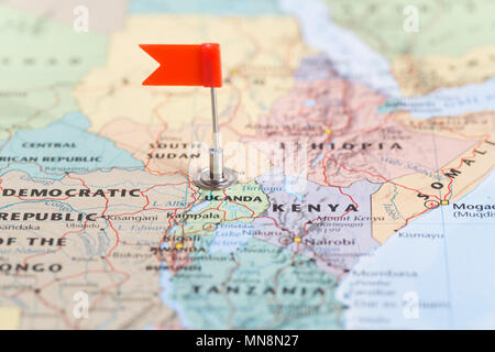 Small red flag marking the African country of Zambia on a world map. - Stock Photo