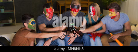 Football fans toasting the game in front of tv - Stock Photo