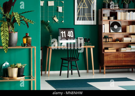 Black chair at desk with desktop computer in green home office interior with wooden furniture - Stock Photo
