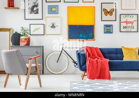 Red blanket thrown on blue settee in bright sitting room interior with patterned armchair, bike and many posters hanging on the wall - Stock Photo