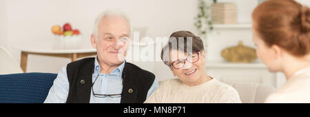 Close-up portrait of happy senior man and woman looking at a counselor in marriage therapy session