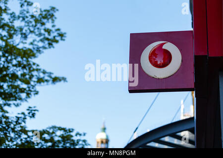 The Vodafone logo displayed on a high street store sign on a sunny day. - Stock Photo