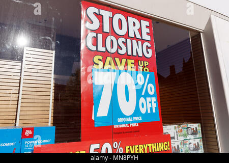 A high street store advertising a store closing down sale with up to 70% off. - Stock Photo