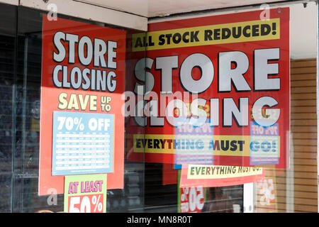 A high street retailer heavily advertising a store closing down sale. - Stock Photo