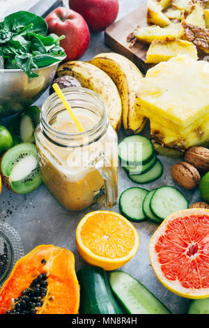 Healthy mango detox  smoothie drink in a glass surrounded by raw fruit ingredients,banana,ananas, papaya,cucumber, kale,spinach, - Stock Photo