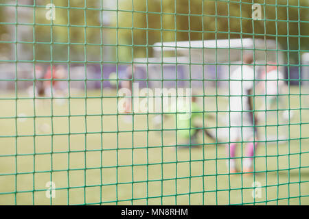 Football, soccer field, soccer gate, view from soccer goal net, blurred stadium, field pitch. Soccer school. Sportsmens, football players on Sports tr - Stock Photo