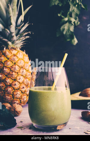 Healthy green smoothie with kalw, banana and date in glass against a dark background. Detox, diet, healthy, vegetarian food concept with copy space. R - Stock Photo