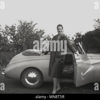 1955, historical, elegant lady wearing a mac type overcoat -dressed for the changing British weather - stands proudly by her soft-top sports car, England, UK. - Stock Photo