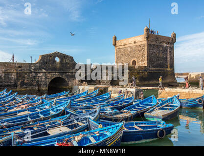 Bright Blue fishing boats moored by the historic Fort in the harbor off of the Atlantic Ocean in the historic port city of Essaouira, Morocco, Africa. - Stock Photo
