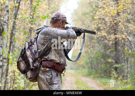 hunter in camouflage taking aim from a shotgun in the wildfowl - Stock Photo