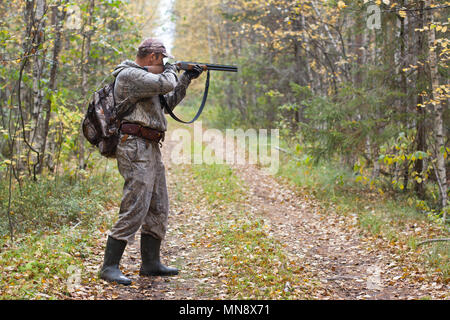 hunter taking aim from a shotgun in the wildfowl - Stock Photo