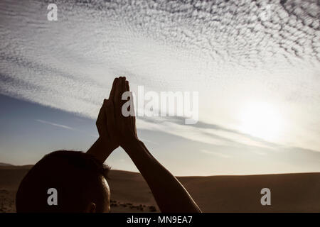 closeup of a young caucasian man practicing yoga outdoors, against a cloudy sky, with the sun in the background - Stock Photo