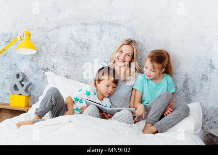 Beautiful mother is reading a story to her children - Stock Photo