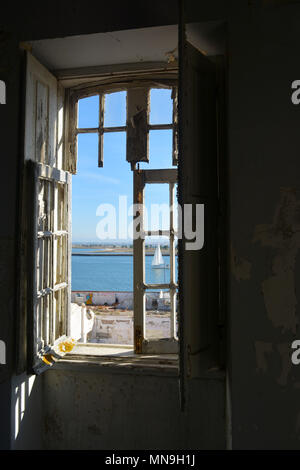 View of a sailing boat from an old, dilapidated window in an abandoned apartment in Portugal - Stock Photo