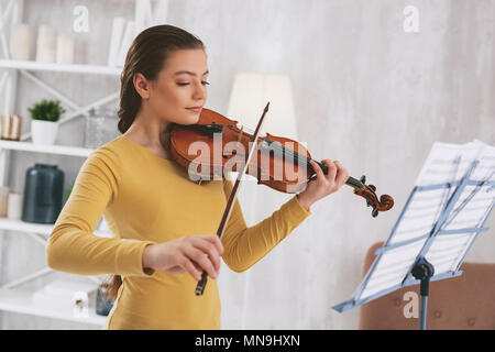 Attentive girl learning classical work - Stock Photo