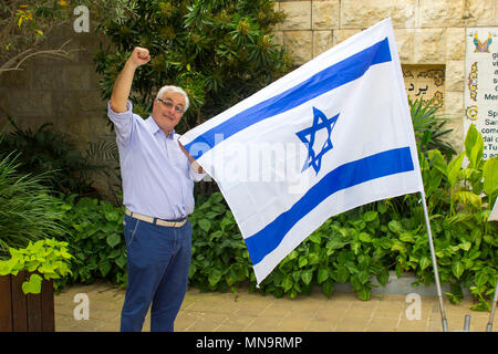 A 70 year old gentile male pumps the air in solidarity with Israel while holding the national flag - Stock Photo
