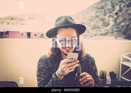 long hair nice young man read and check the phone on the roofteop terrace outdoor. black hat and eyeglasses and tattoo on hand. fashion model sith nic - Stock Photo