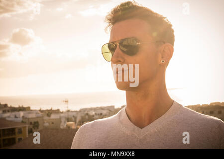 beautiful young man with sunglasses like aviator model looking in front. beautiful golden sunset on the background with ocean and amazing view from hi - Stock Photo